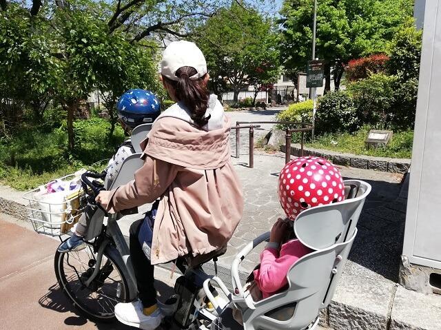 子ども2人乗せて自転車に乗るママ